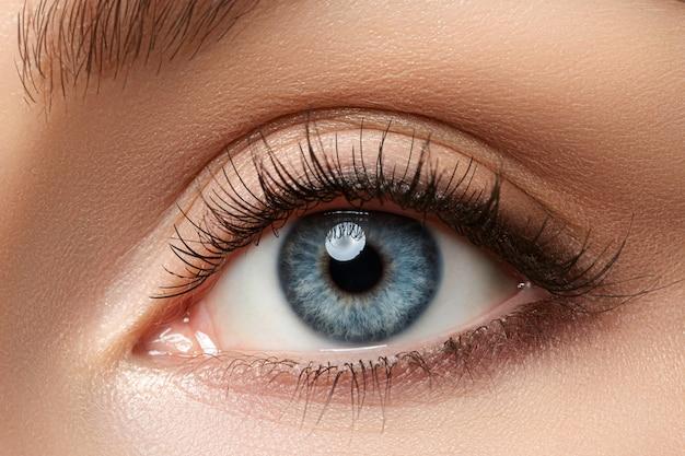 Close-up van mooie blauwe vrouwelijke oog. goed zicht, contactlenzen, vertrouwen of observatieconcept