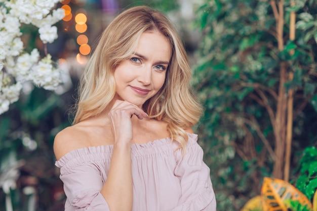 Close-up van mooie blonde jonge vrouw met kin op haar hand