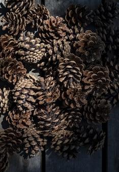 Close-up van mooie dennenappels opgestapeld samen in een donkere plaats