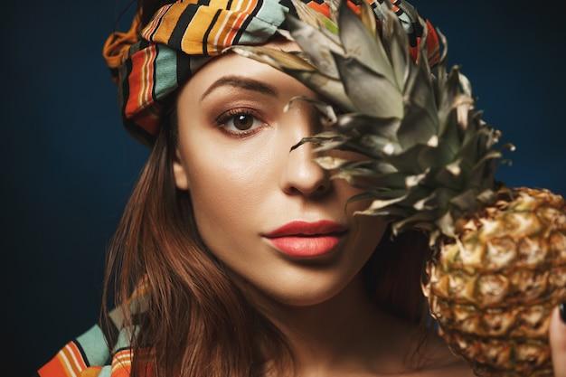 Close-up van mooie exotische vrouw in hoofdband. geïsoleerd op blauw. met ananas,