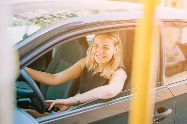 Close-up van mooie glimlachende jonge vrouw die de auto drijft