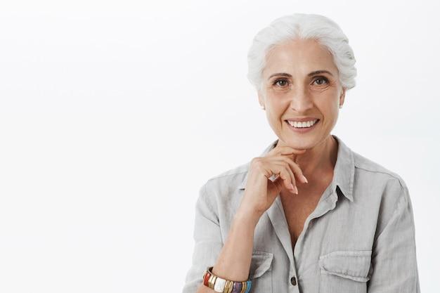 Close-up van mooie glimlachende oude dame die tevreden en geïnteresseerd kijkt