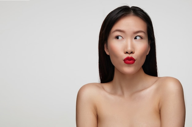 Close-up van mooie jonge bruinogige brunette vrouw haar lippen vouwen in lucht kus en opzij kijken met belangstelling, poseren over witte muur met blote schouders