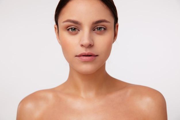Close-up van mooie jonge brunette groenogige vrouw met natuurlijke make-up oprecht kijken, staande met blote schouders
