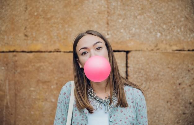 Close-up van mooie jonge brunette tienermeisje die roze kauwgom blaast over een stenen muur