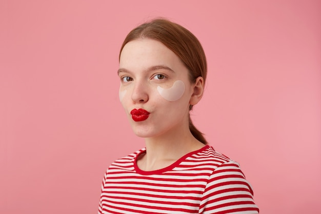 Close-up van mooie jonge lachende roodharige dame met rode lippen en met vlekken onder de ogen, draagt in een rood gestreept t-shirt, kijkt en stuurt kus, staat.
