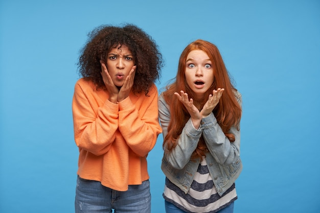 Close-up van mooie jonge vriendinnen in vrijetijdskleding die handen opsteken naar hun verbaasde gezichten terwijl ze verbaasd kijken, geïsoleerd over blauwe muur