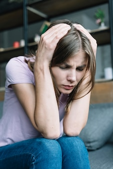 Close-up van mooie jonge vrouw die aan hoofdpijn lijdt