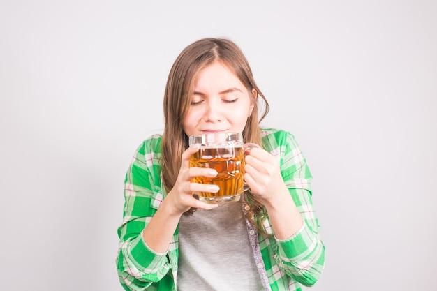 Close-up van mooie jonge vrouw die bier test.