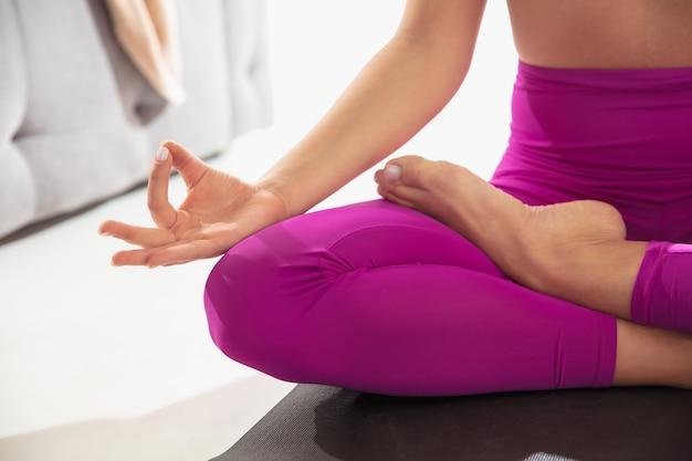 Close up van mooie jonge vrouw die binnenshuis aan het trainen is en yoga-oefening doet op grijze mat details