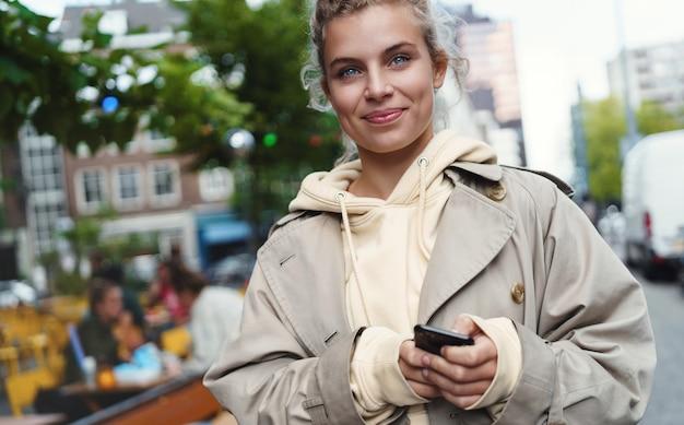 Close-up van mooie jonge vrouw die zich op straat met mobiele telefoon bevindt en gelukkig glimlacht.