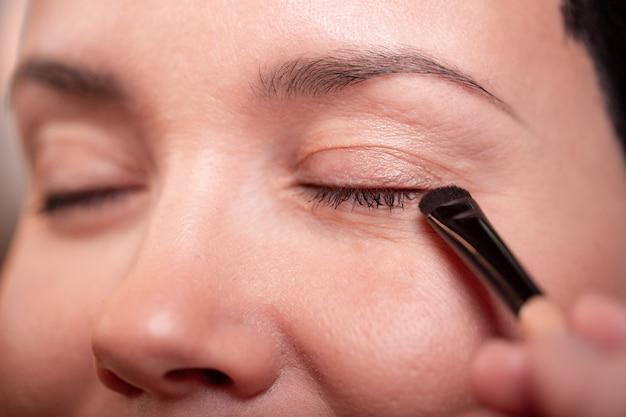 Close-up van mooie jonge vrouw gezicht met make-up, frisse zachte huid en lange zwarte dikke wimpers mascara met cosmetische borstel toe te passen. make-up en cosmetica concept. hoge resolutie