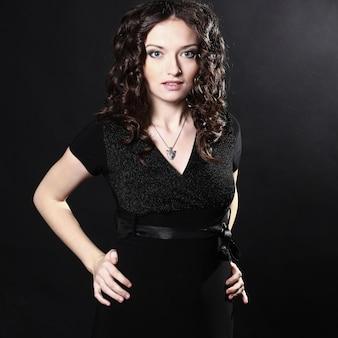 Close-up van mooie jonge vrouw in zwarte avondjurk. geïsoleerd op zwarte muur