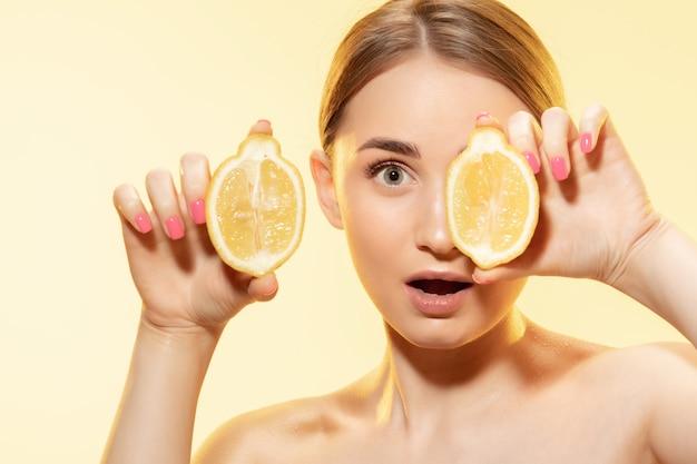 Close up van mooie jonge vrouw met avocado op gele achtergrond