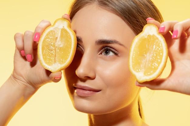 Close up van mooie jonge vrouw met plakjes citroen op gele achtergrond. concept van cosmetica, make-up, natuurlijke en eco-behandeling, huidverzorging. glanzende en gezonde huid, mode, gezondheidszorg.