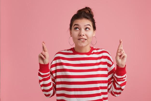 Close-up van mooie jonge vrouw met sproeten, draagt gestreepte longsleeve, houdt vingers gekruist, bijt op zijn lip en kijkt naar copyspace geïsoleerd over roze muur. veel geluk wensen.