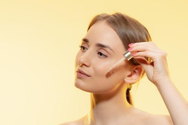 Close up van mooie jonge vrouw met stromend serum, olie op geel