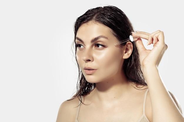 Close up van mooie jonge vrouw over witte muur. glanzende en gezonde huid, mode, gezondheidszorg.
