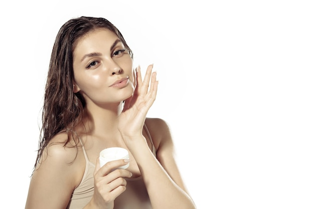 Close up van mooie jonge vrouw over witte muur. glanzende en gezonde huid