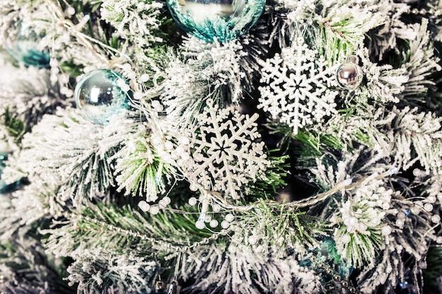 Close-up van mooie kleurenkerstversieringen die op kerstboom hangen.