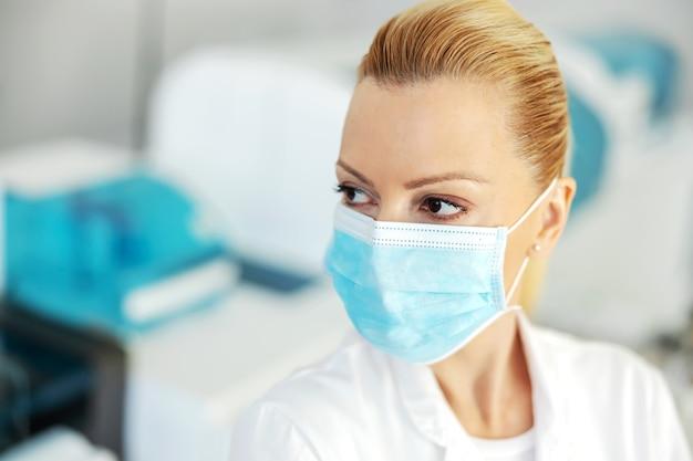 Close-up van mooie laboratoriummedewerker met beschermend steriel gezichtsmasker. covid 19-uitbraakconcept.