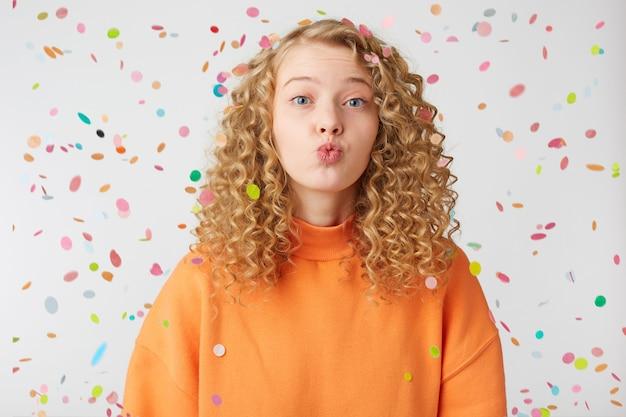 Close-up van mooie lieve mooie blonde meisje lucht kus direct naar voren sturen met tedere blik, staat onder vallende confetti