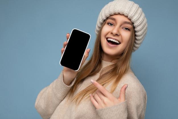 Close-up van mooie positieve jonge vrouw stijlvolle beige trui en beige gebreide winter hoed dragen