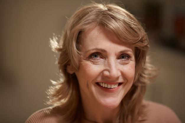 Close-up van mooie rijpe vrouw met blond haar glimlachend in de camera