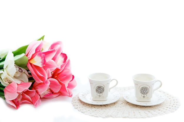 Close up van mooie rode tulpen in vaas en twee kopjes op een witte achtergrond. kopieerruimte.