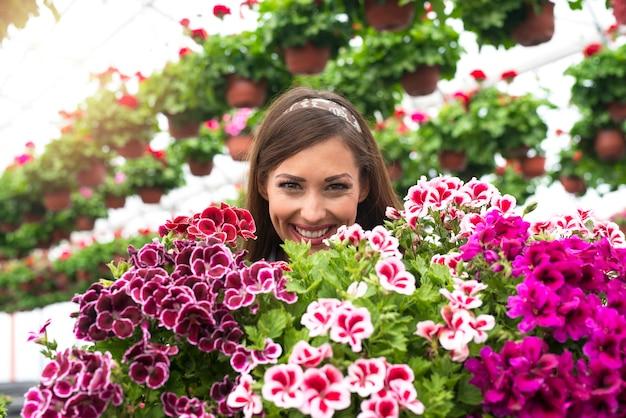 Close-up van mooie schattige blanke vrouw bloemist gezicht omgeven door bloemen in serre tuin.