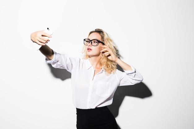 Close-up van mooie speelse zakenvrouw selfie foto maken op geïsoleerde witte muur