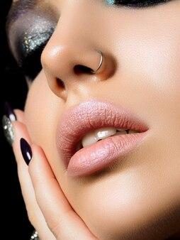 Close-up van mooie vrouw aanraken van haar gezicht met perfecte huid en avond make-up