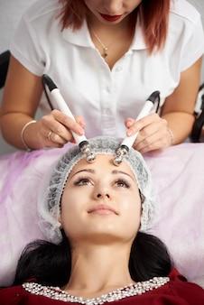 Close-up van mooie vrouw die gezichts microstroombehandeling van therapeut ontvangen bij kuuroordsalon. schoonheidsspecialiste die elektrische impulsen gebruikt voor gezichtsprocedures. cosmetologie.