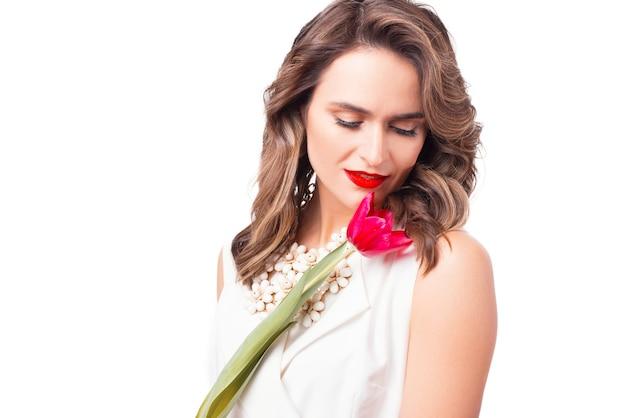 Close-up van mooie vrouw ruikende roze tulp op wit