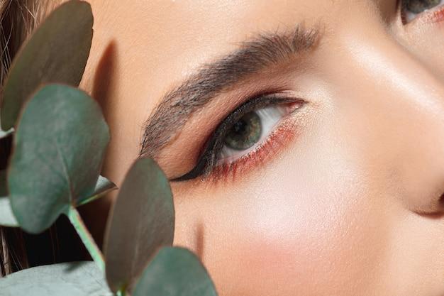 Close up van mooie vrouwelijke gezicht met biologische behandeling op wit.