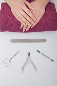 Close-up van mooie vrouwelijke handen die kuuroordmanicure hebben bij schoonheidssalon