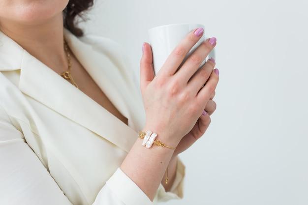 Close up van mooie vrouwelijke handen met grote witte kopje cappuccino koffie.