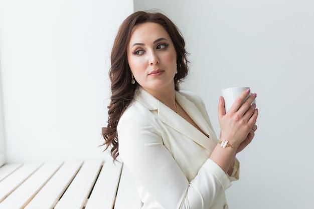 Close up van mooie vrouwelijke handen met grote witte kopje cappuccino koffie