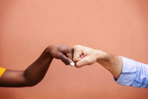 Close-up van multiculturele vrienden die vuistbult aan elkaar geven.