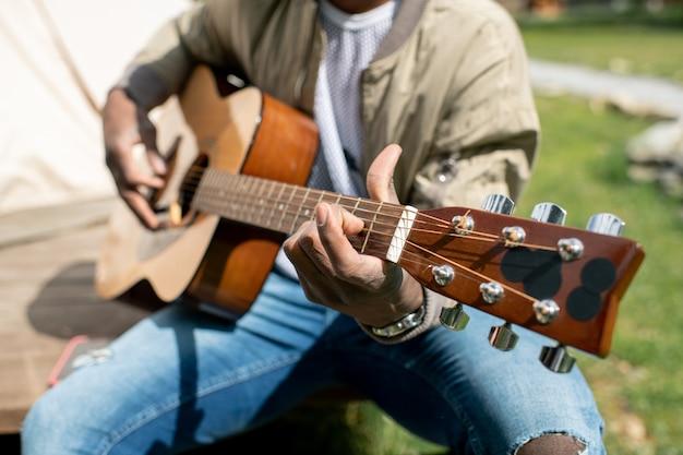 Close-up van muzikant akoestische gitaar buiten spelen terwijl u geniet van kamperen