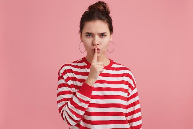 Close-up van mysterieus meisje, toont een gebaar van stilte, met een wijsvinger bij de mond, roept op tot privacy, geheim, blijf rustig, kalm, geïsoleerd.