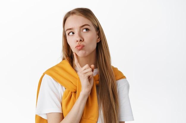 Close-up van nadenkende jonge vrouw, peinzend gezicht makend, kin en tuit lippen aanraken, kijken naar productpromo in de rechterbovenhoek terwijl ze denken, keuze maken, over witte muur staan