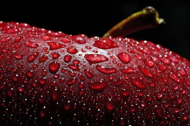 Close-up van natte appel tegen zwarte achtergrond