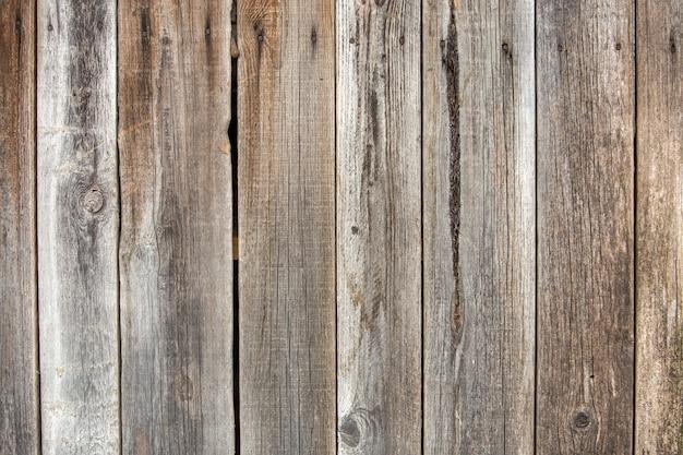 Close-up van natuurlijke oude vintage verweerde grijs bruin ongeverfd massief houten hek of poort van planken en planken.