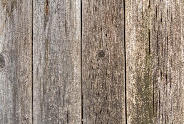Close-up van natuurlijke oude vintage verweerde grijsbruin ongeverfd massief houten hek of poort van planken en planken. de ecologische ruimte zonnige geknapperde achtergrond van het textuur verticale exemplaar.