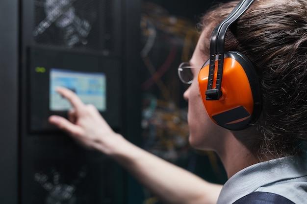 Close-up van netwerkingenieur die serverkast bedient via digitaal bedieningspaneel in datacenter, kopieer ruimte