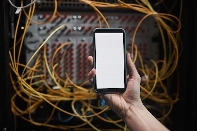 Close-up van netwerkingenieur die smartphone met leeg scherm in serverruimte vasthoudt tijdens onderhoudswerkzaamheden in datacenter, kopieer ruimte