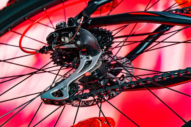 Close-up van nieuwe fiets achterderailleur in rode kunstmatige bliksem wordt geschoten die