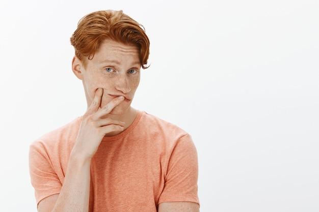 Close-up van nieuwsgierige roodharige man op zoek geïntrigeerd, keuze maken
