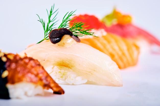 Close-up van nigirisushi met zalm, tonijn, kaviaar en paling worden geplaatst die